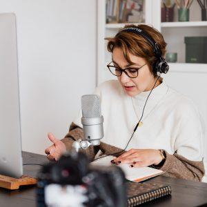 mujer con auriculares y micrófono frente a una computadora